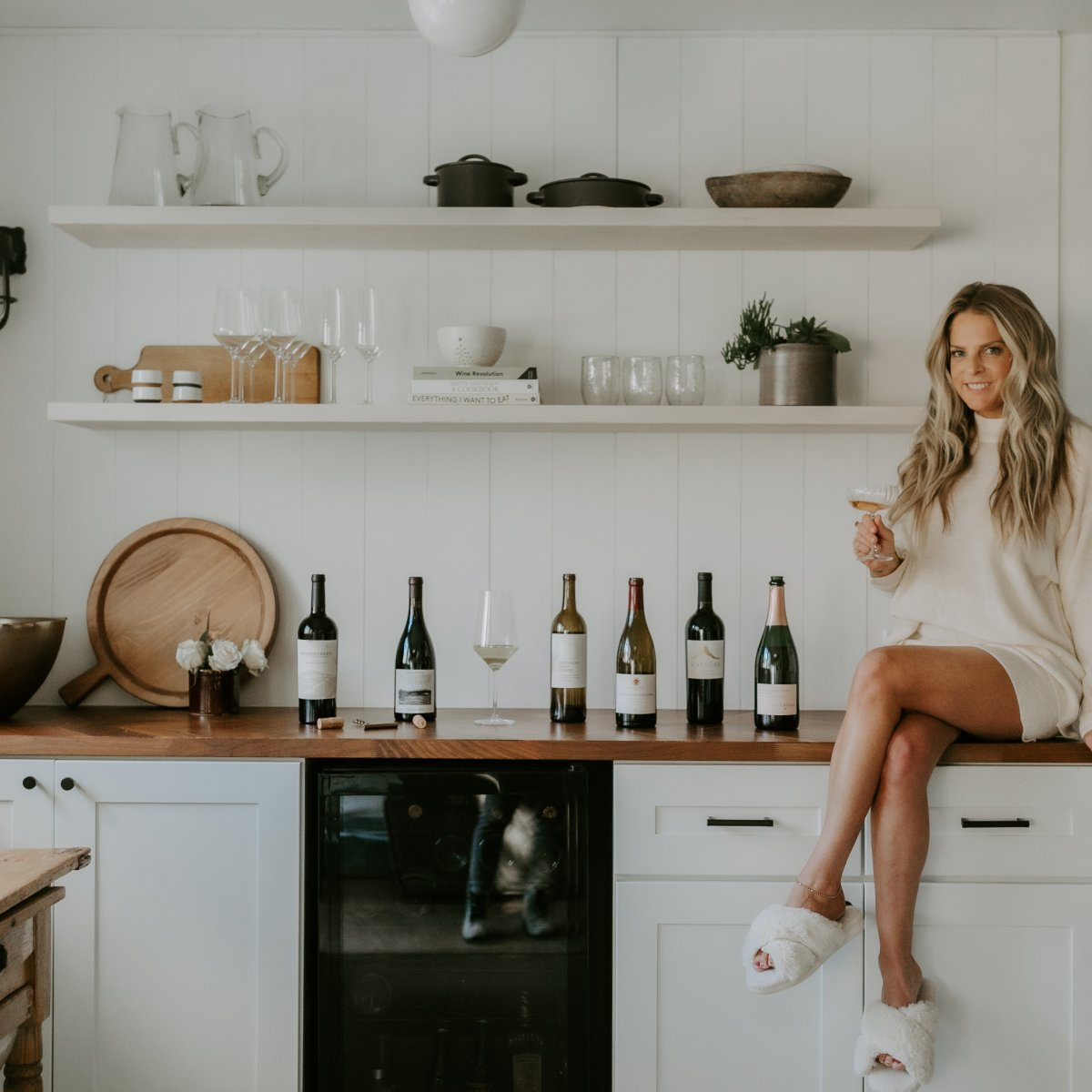 Woman Sitting on Counter with Wine