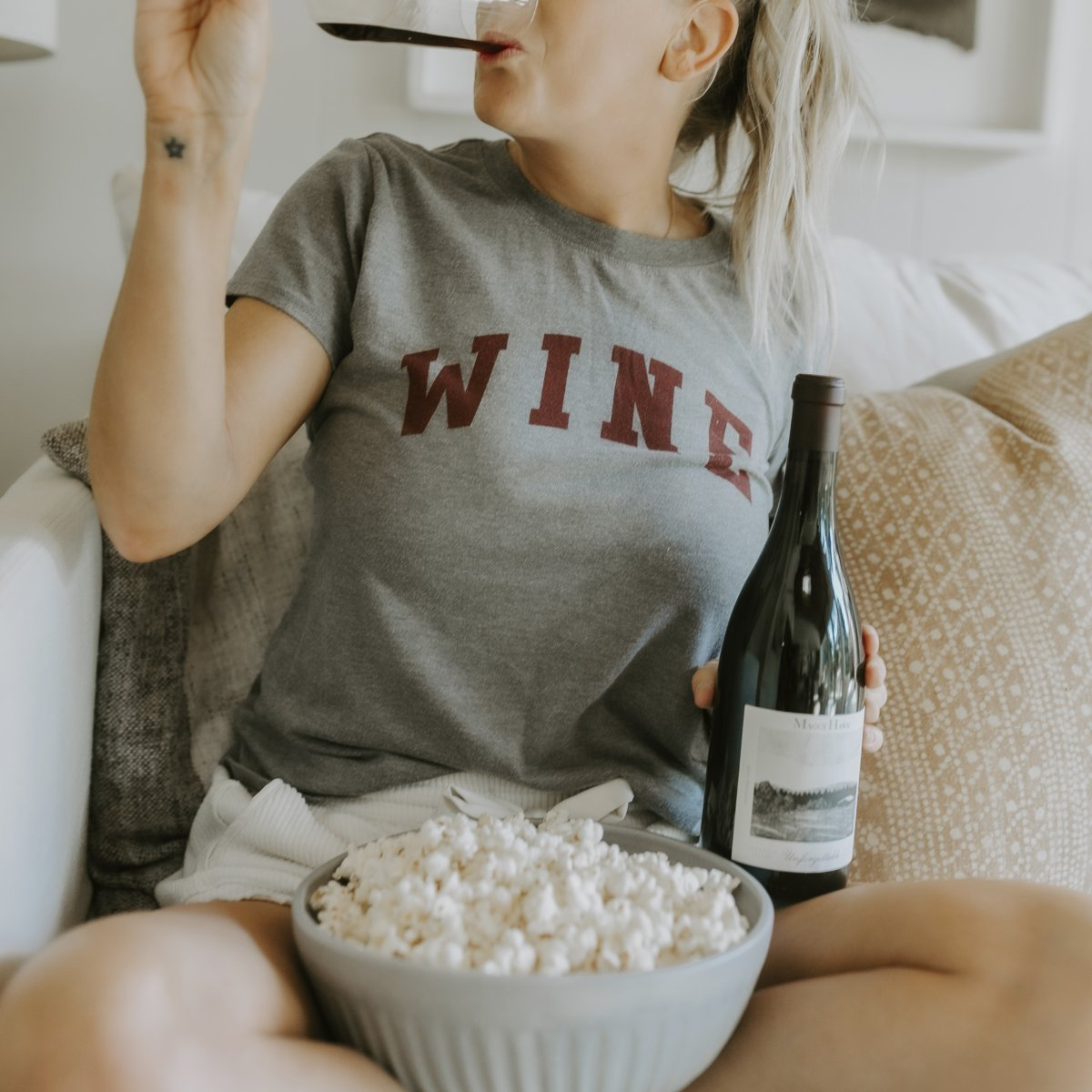 Woman Drinking a Glass of Wine with Popcorn in a Bowl in Front of Her