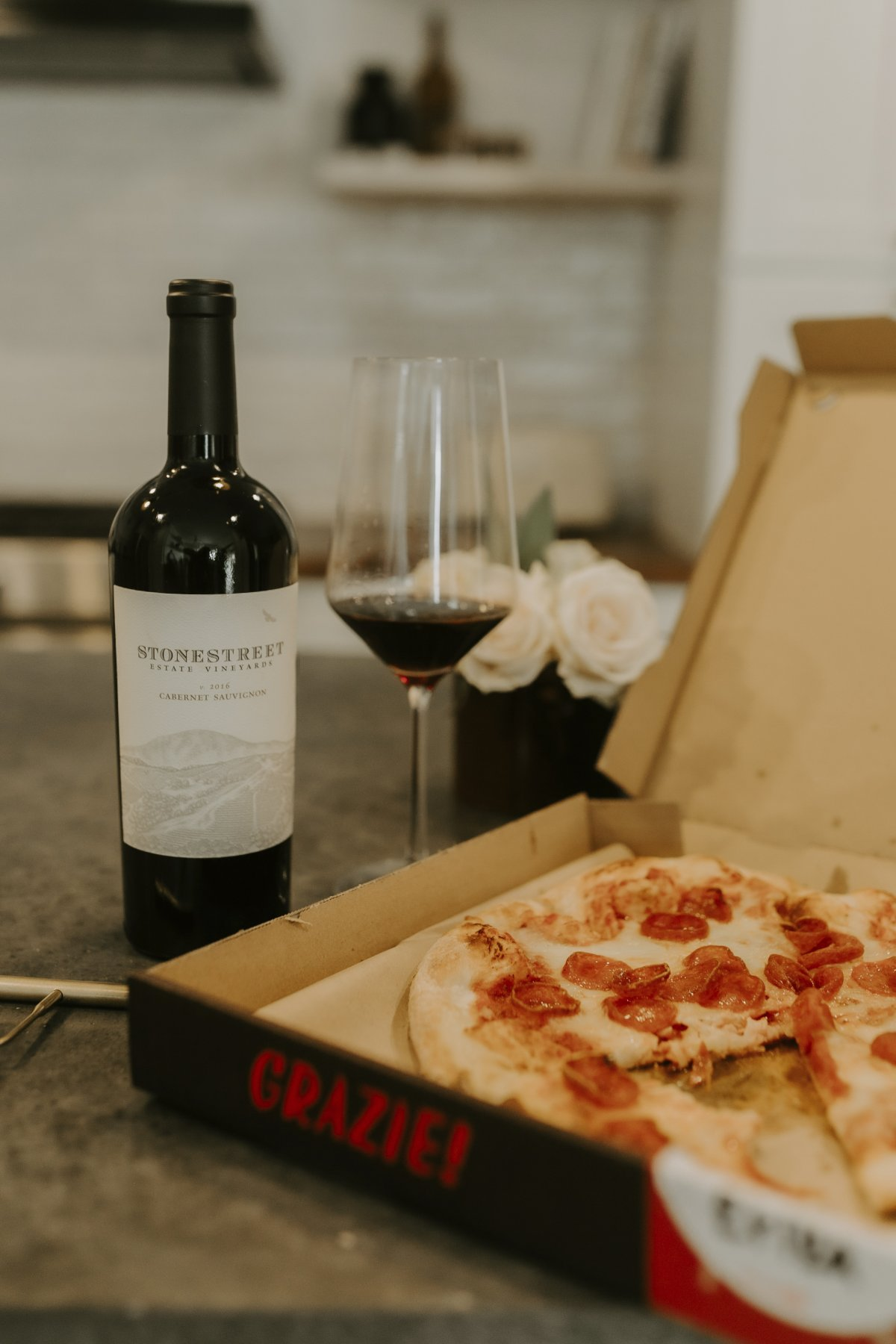 Bottle of Wine and Glass of Red Wine Next to a Pizza