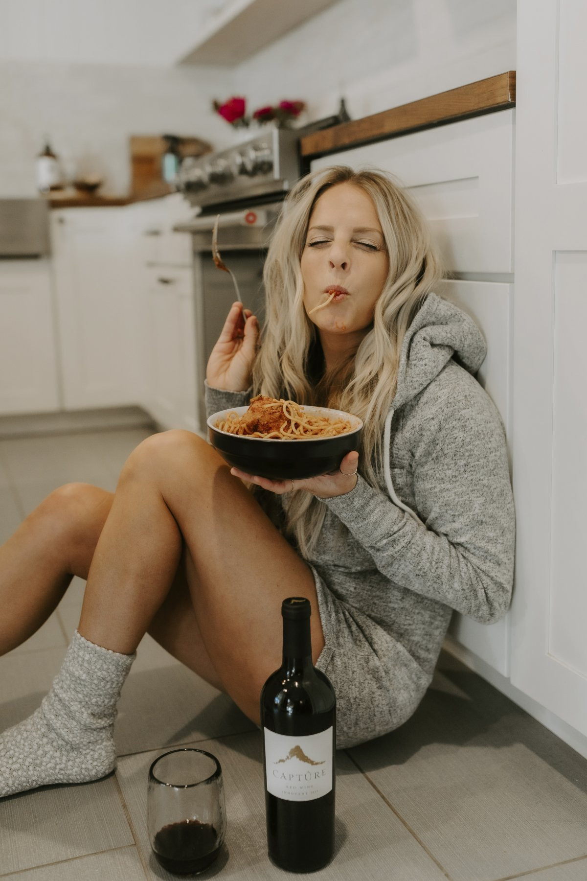 Woman Sitting on the Floor Eating Spaghetti with Wine Bottle and Glass Sitting on Floor