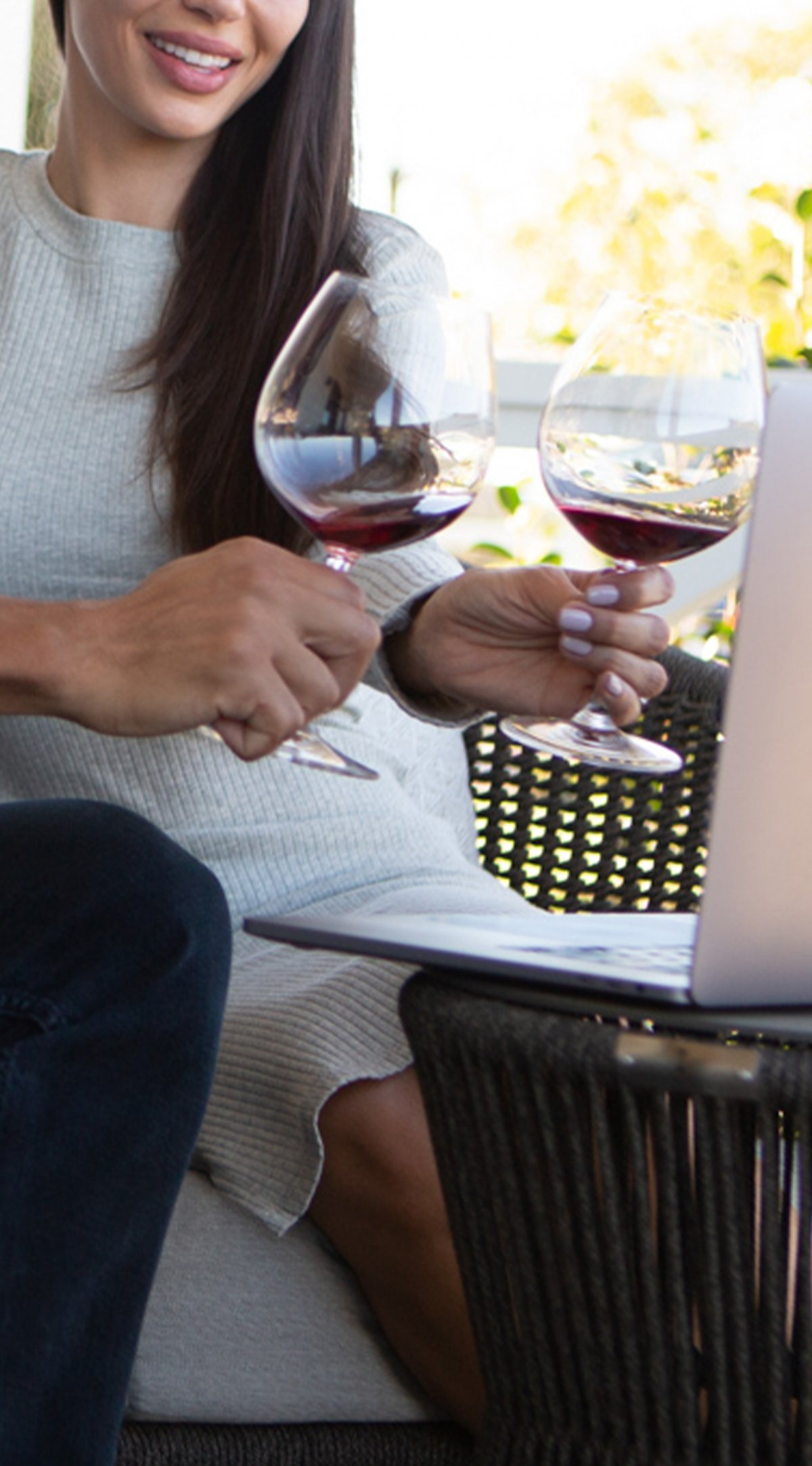 Woman with wine in front of a computer screen