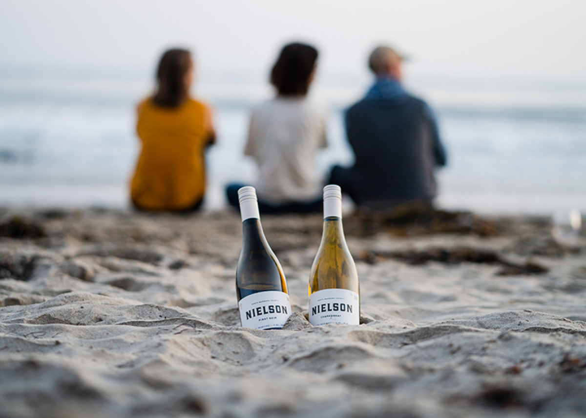 Two wine bottles in the sand on the beach